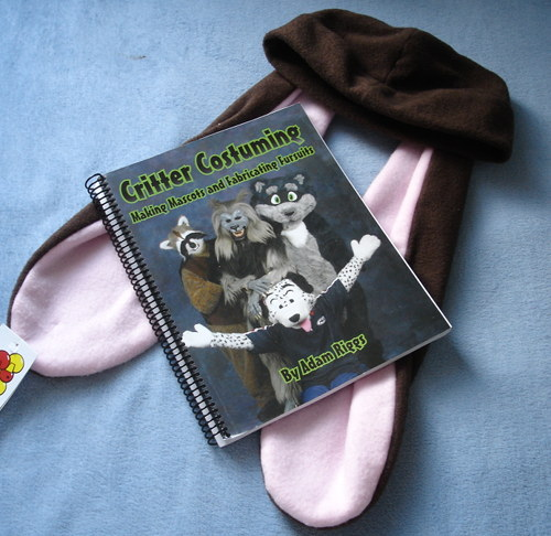 A spiral-bound book atop a brown hat, which have two chocolate colored bunny ears extending from it. The cover of the book displays Critter Costuming: Making Mascots and Fabricating Fursuits.